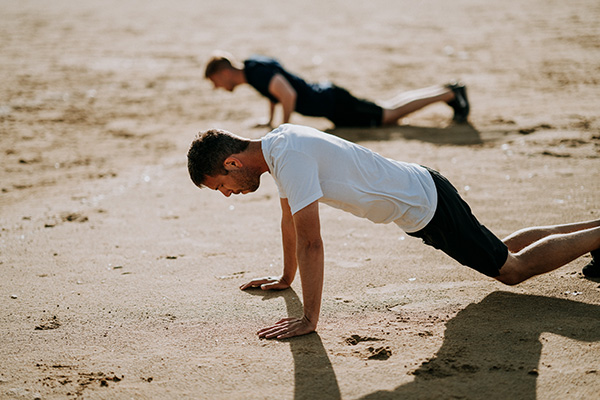 Two Men Doing Push Ups in the Sand