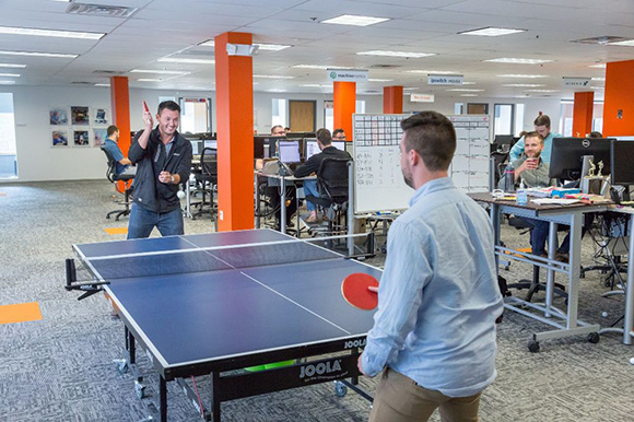 Two People Playing Ping Pong at Work