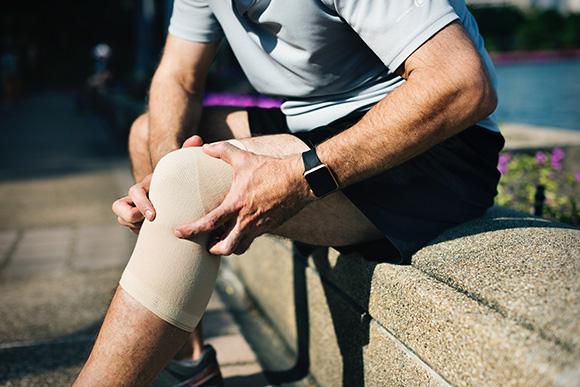 Man Holding Knee Braced