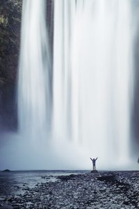 waterfall with person arms up