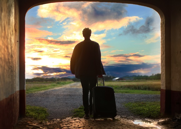 man with suitcase sunset