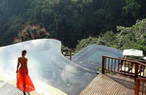 Woman in Red Dress overlooks Bali Hanging Gardens Infinity Pool Bali