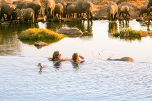 Infinity Pool next to Elephant Water Hold Two Women enjoy