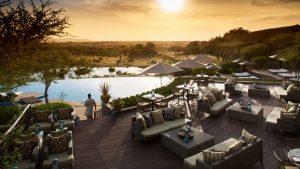 Waiter walks with drinks at sunset at Four Seasons Safari Pool