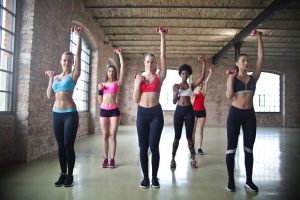 Group Of Women Facing Camera Exercising with dumbbells