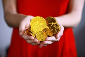 outstretched hands with gold coins