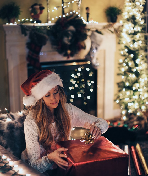 Woman Opening A Christmas Present With LIghts in Background