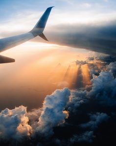 Plane Tail Above Clouds and Sun