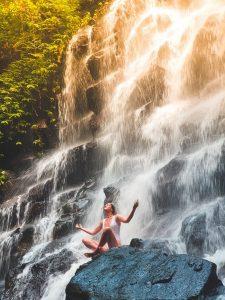 woman meditating at a waterfall