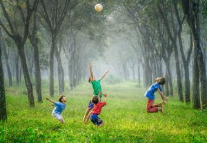 4 boys Playing on Green Grass with Trees In Back