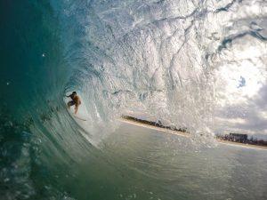 Man Surfing under A Wave