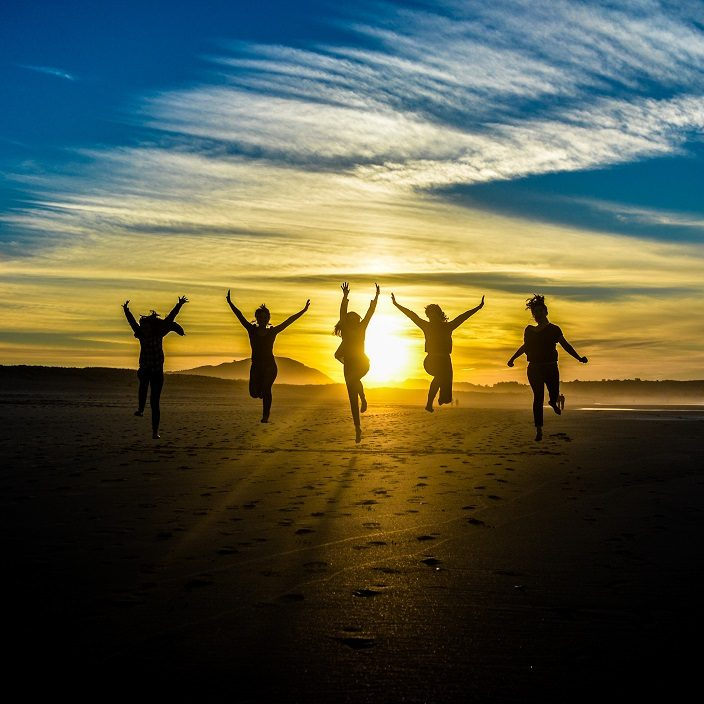 Beautiful Sunset With People Silhouettes Jumping hands outstretched.